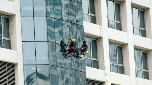 two men cleaning personnel are hanging with wire safety belt to wipe windows mirror - cleaner stock videos and b-roll footage