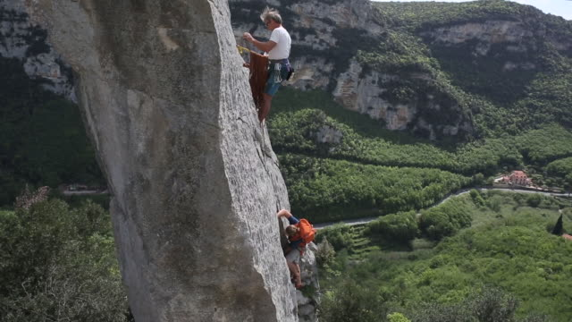 Two men climb limestone pinnacle, mountains behind