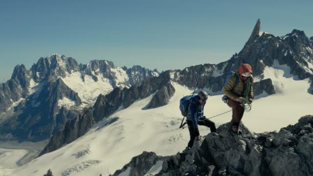 二人の男が山の頂上に登る - クライミング点の映像素材/bロール