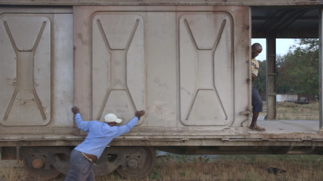 two men close the sliding door on a box car carriage. - pushing stock videos and b-roll footage