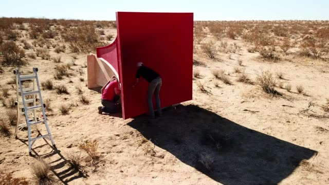 stockvideo's en b-roll-footage met two men constructing large, red object in desert scrubland - groot
