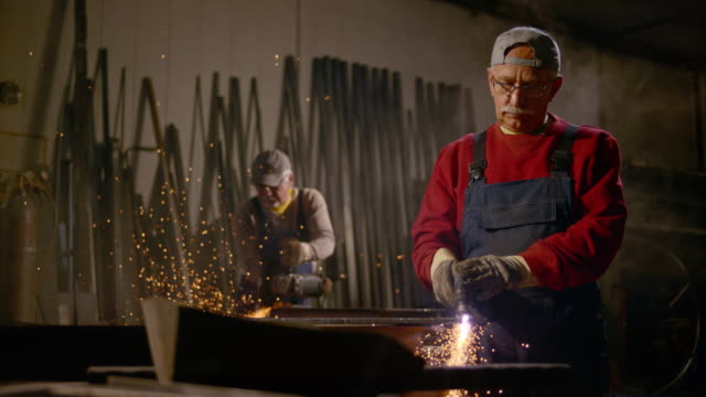 SLO MO LD Two men cutting metal in the workshop