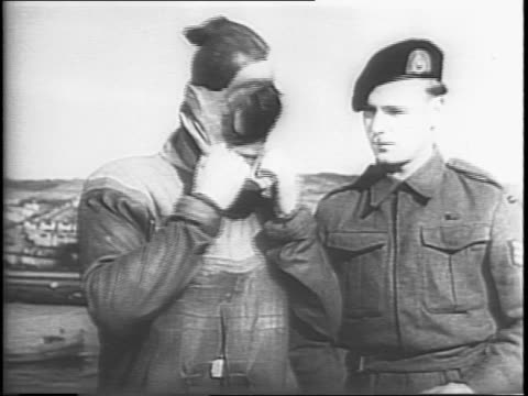 vídeos de stock, filmes e b-roll de two men demonstrating a frogman wet suit for a group of seated men / man being helped in to a wet suit / man putting on the mask for the wet suit /... - diving suit