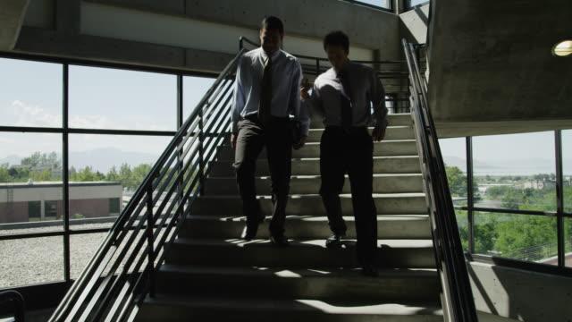vídeos de stock, filmes e b-roll de ws td two men descending office stairs / orem, utah, usa - orem utah