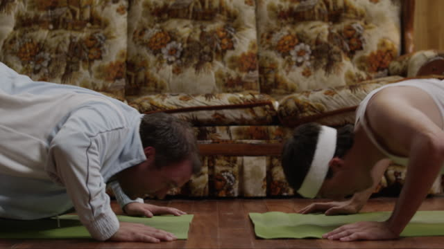 vídeos de stock e filmes b-roll de ms tu two men doing yoga on exercise mats in living room / orem, utah, usa - orem