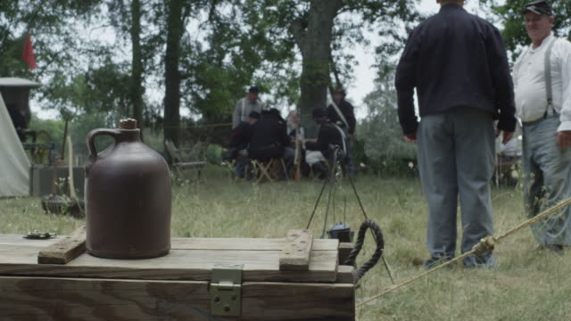 stockvideo's en b-roll-footage met two men dressed as civil war soldiers grab a jug from a wooden plank and walk toward the camp. - men