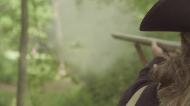 two men dressed as revolutionary war soldiers fire muskets in woods - army soldier stock-videos und b-roll-filmmaterial