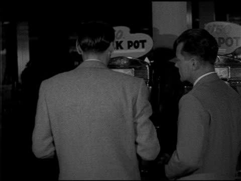 two men dressed in suits playing 'jack pot' slot machine man putting in coins pulling arm handle twice moving to give other man a turn 'onearmed... - 1952 stock videos and b-roll footage