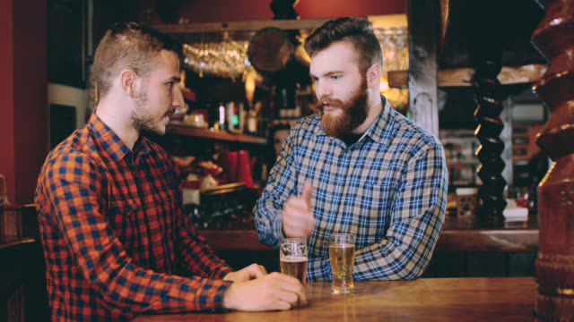 ds two men drinking beer in the pub - table top shot video stock e b–roll