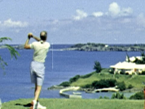 montage two men drive golf balls off of tees overlooking water. woman sinks a putt while man holds flag / bermuda - bermuda stock videos & royalty-free footage
