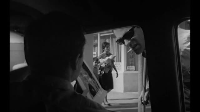 vídeos y material grabado en eventos de stock de 1959 two men driving along pull over to show man image of missing scientist on clipboard - montaje documental
