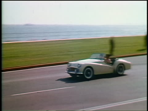 1963 PAN two men driving convertible in traffic on coastal road / California / educational