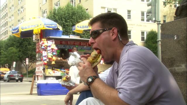 two men eat hot dogs near a hot dog stand. - hot dog stock videos & royalty-free footage