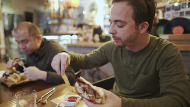 two men eating burgers - cheeseburger stock videos & royalty-free footage