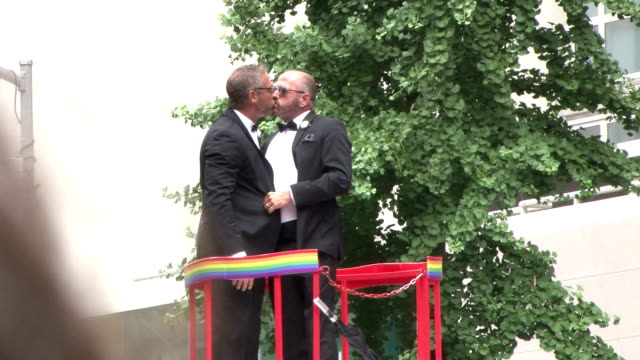 two men embrace with a kiss at the annual gay pride parade in new york city, celebrating the recent supreme court ruling making same sex marriage... - new york stato video stock e b–roll