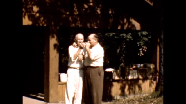 1953 Two Men Embracing and Sharing Cigarettes