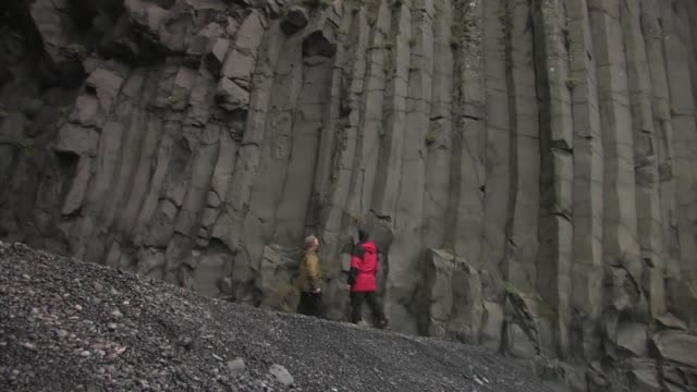 two men examining a wall of columnar basalt rock. editorial use only. - basalt stock videos & royalty-free footage
