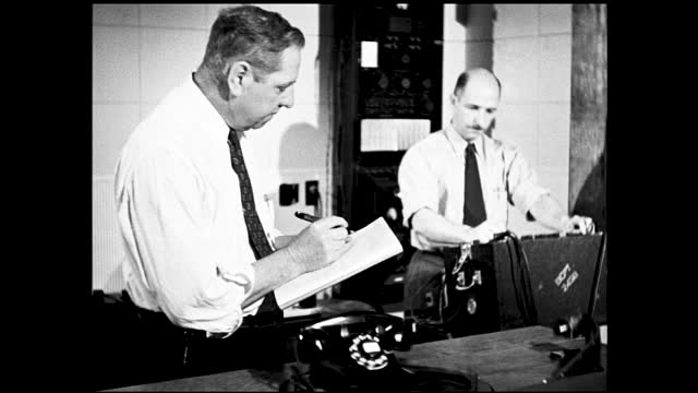 vidéos et rushes de two men experimenting with telephone; machine spins as arm waves back and force, man writes down something on the clipboard - 1940 1949