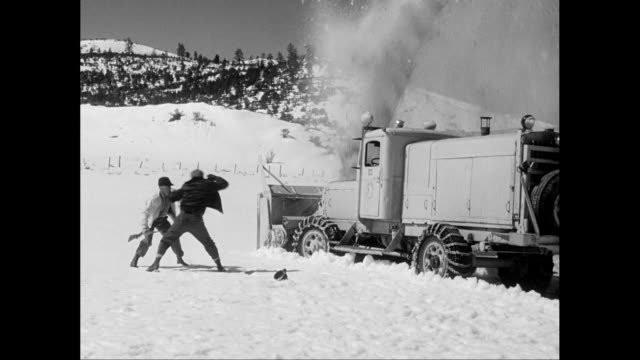 MS PAN Two men fall out of truck plowing snow, fight and wrestle as the truck continues in the snow / United States