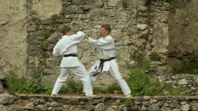 WS SLO MO PAN Two men fighting karate on kamen castle / Begunje na Gorenjskem, Slovenia