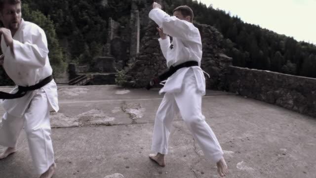 vídeos de stock, filmes e b-roll de ws two men fighting karate on kamen castle / begunje na gorenjskem, slovenia - karate
