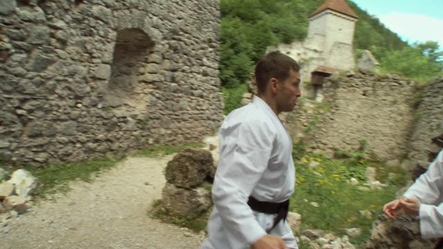 vídeos de stock, filmes e b-roll de ws zi zo two men fighting karate on kamen castle / begunje na gorenjskem, slovenia - karate