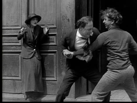 1915 b/w ms two men fighting over woman cowering by wall, then one man is shot - femmina con gruppo di maschi video stock e b–roll