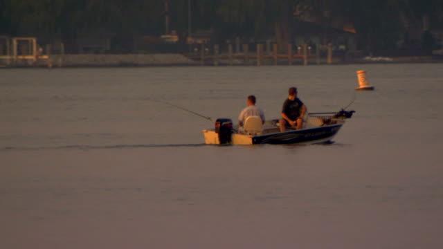 vídeos de stock, filmes e b-roll de two men fishing and cruising along in lake michigan - passear sem destino