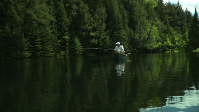 ws two men fishing from canoe on scenic lake surrounded by evergreen trees, morristown, vermont, usa - fishing rod stock videos & royalty-free footage