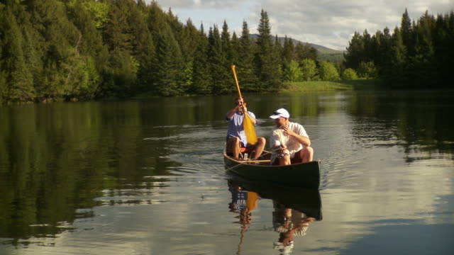vidéos et rushes de ws ms two men fishing from canoe on scenic lake surrounded by evergreen trees, morristown, vermont, usa - lancer la ligne de canne à pêche