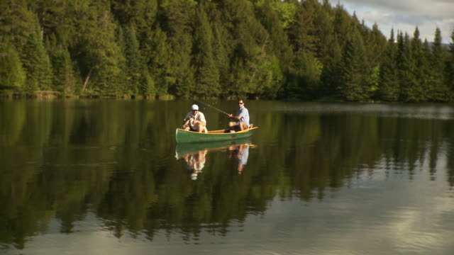 WS Two men fishing from canoe on scenic lake surrounded by evergreen trees, Morristown, Vermont, USA