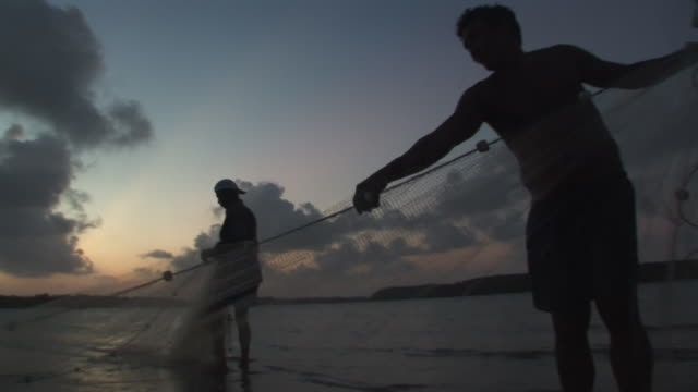 ms two men fishing with net during sunset / ilha dos lencois, maranhao, brazil - fishing industry stock videos & royalty-free footage