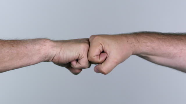 Two men fist bumping and hand shaking