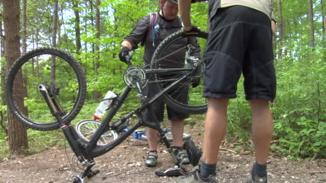 ms tu zi cu two men fixing bike chain in bedgebury forest / kent, england, uk - see other clips from this shoot 1036 stock videos and b-roll footage