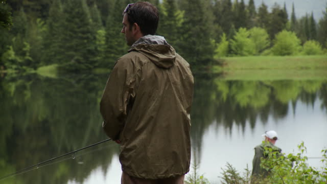 ms td, two men fly fishing by lake in rainy day, morristown, vermont, usa - fishing rod stock videos & royalty-free footage