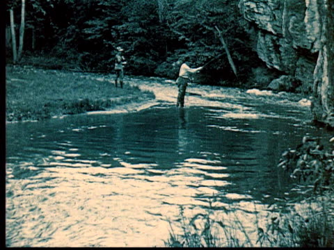 vidéos et rushes de 1924 b/w montage two men fly fishing in stream. one catches fish + puts into net / south dakota, usa - 1924