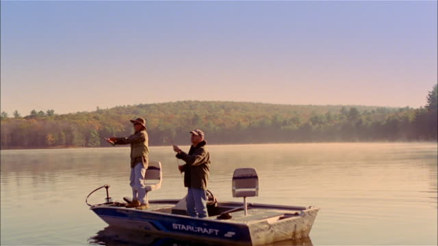 MS, two men fly fishing standing on fishing boat on lake, USA, Pennsylvania