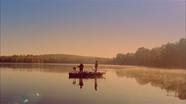 WS, two men fly fishing standing on fishing boat on lake, USA, Pennsylvania