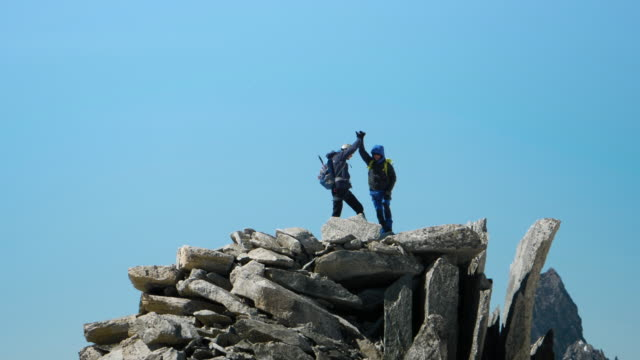 two men, friends high five on top of the mountains. - ridge stock videos & royalty-free footage