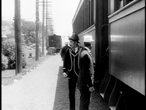 1910 b&w two men getting into train and moving off/ usa - 1910 stock-videos und b-roll-filmmaterial
