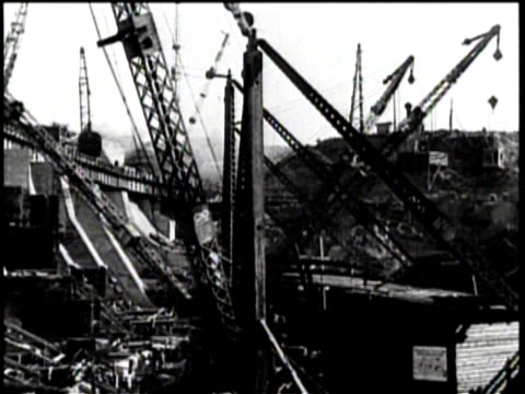 two men go down a river on a raft / construction is underway on a dam / large cranes move supplies / men work at the construction site / one man... - ehemalige sowjetunion stock-videos und b-roll-filmmaterial