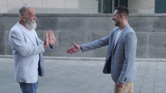 vídeos y material grabado en eventos de stock de dos hombres se saludan con nuevos apretones de manos y saludos. dos personas - codo
