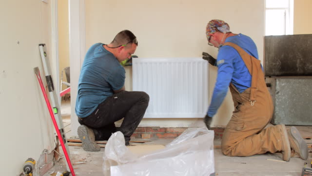 two men hanging a radiator - installing stock videos & royalty-free footage