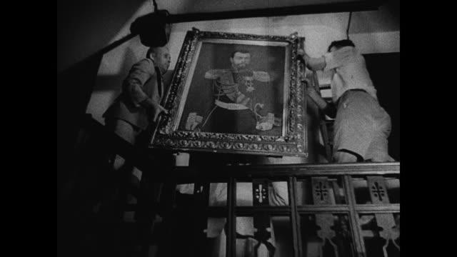Two men hanging painted portrait of Czar Nicolas II