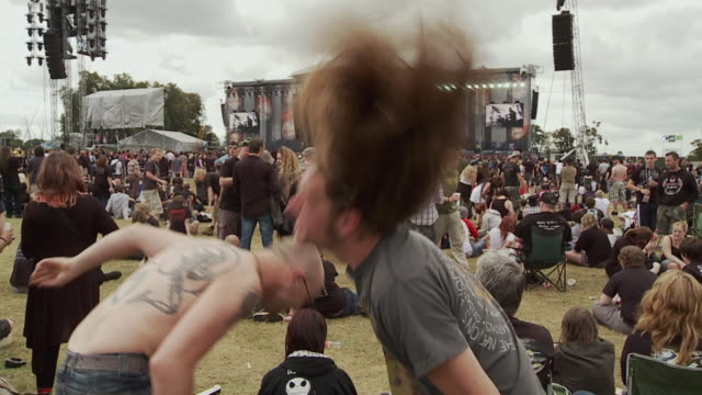 ms slo mo two men head banging at music festival, music stage in background / knebworth, hertfordshire, uk - rock stock videos & royalty-free footage