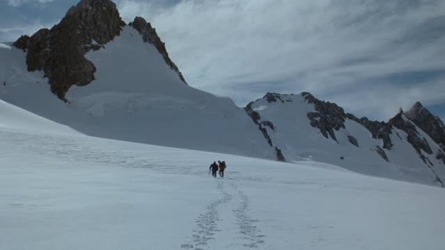 vídeos y material grabado en eventos de stock de ws two men hiking across snowy landscape toward mountain in mt cook national park/ south island, new zealand  - pisada