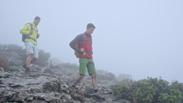 二人の男が重い霧の山をハイキング - ツレス点の映像素材/bロール