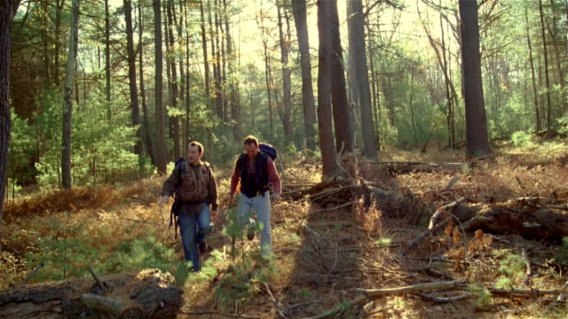 Two men hiking in woods wearing backpacks