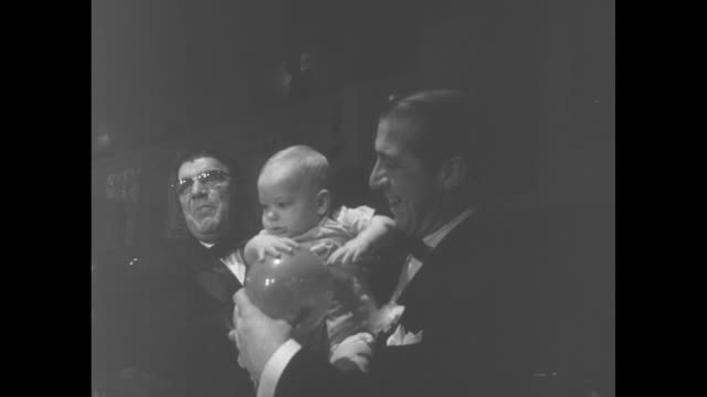 WS two men hold a baby as they stand behind ice sculpture 25 at Variety Club International 25th anniversary celebration / CU William Finkel outgoing...