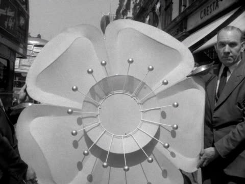 Two men hold a large model of a Tudor rose which are decorating the exteriors of buildings on Regent Street to celebrate the coronation of Elizabeth...